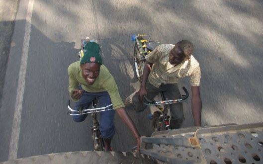 """Two cyclists """"hitching"""" a ride as we drive out of Kigali into the mountains"""